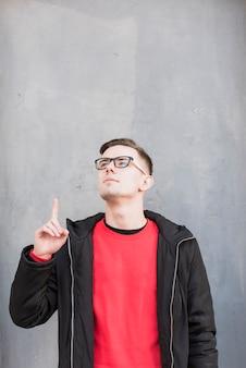 Knappe jonge mens die zijn vinger naar boven richt die omhoog tegen concrete muur kijkt