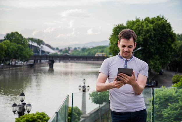 Knappe jonge mens met een tablet in zijn handen die en zich dichtbij de rivier bij europese stad bevinden glimlachen
