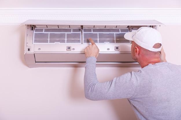 Knappe jonge mensenelektricien die airconditioning installeren in een cliënthuis. reiniging van de airconditioning. man in handschoenen controleert het filter.