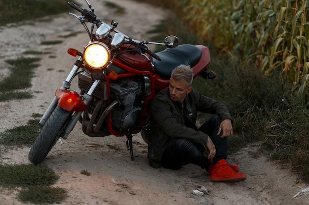Knappe jonge model man in een stijlvolle militaire kaki jas zit 's avonds in de buurt van een motorfiets met licht in een veld. conceptreizen