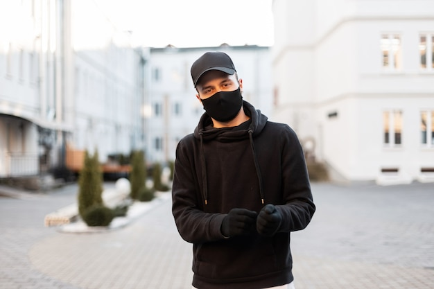 Knappe jonge model man met beschermend medisch masker en stijlvolle pet in modieuze zwarte hoodie en handschoenen in de stad. mannelijke moderne stedelijke stijl en pandemie