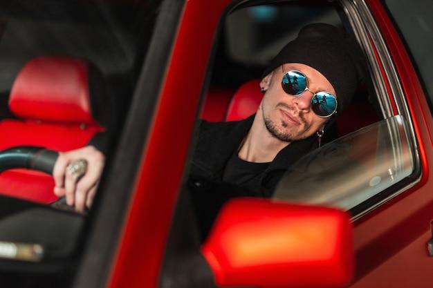 Knappe jonge modelbestuurder met zonnebril berijdt een uitstekende rode auto