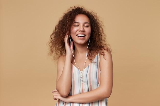 Knappe jonge mooie bruinharige krullende vrouw die haar ogen gesloten houdt en aangenaam lacht terwijl ze geniet van muzieknummer in haar koptelefoon, geïsoleerd op beige