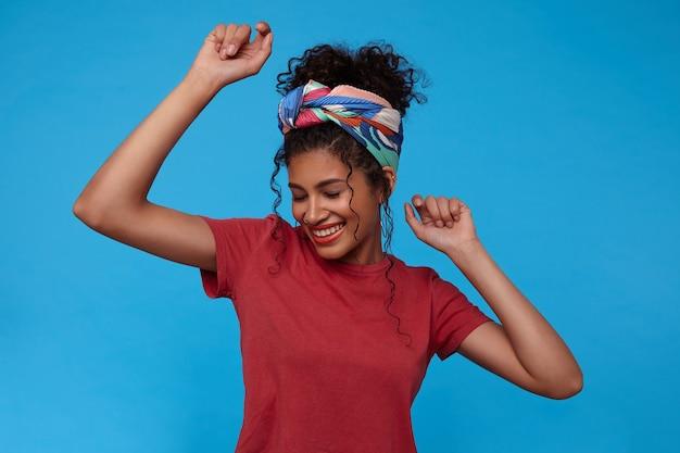 Knappe jonge mooie brunette krullende vrouw met verzameld haar glimlachend vrolijk met gesloten ogen tijdens het dansen met opgeheven handen, poseren over blauwe muur