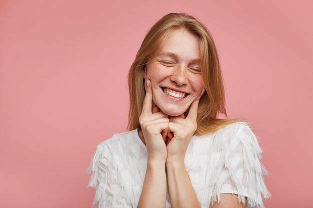 Knappe jonge mooie roodharige dame met natuurlijke make-up houdt wijsvingers op haar wangen en lacht gelukkig met gesloten ogen, staande tegen roze achtergrond