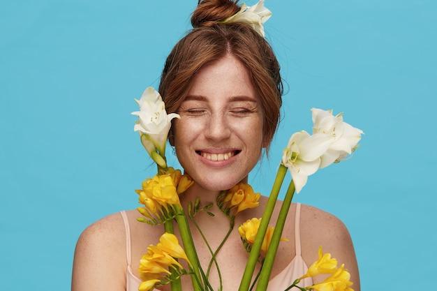 Knappe jonge mooie roodharige vrouw met natuurlijke make-up die haar ogen gesloten houdt terwijl ze vrolijk lacht, een bos bloemen vasthoudt terwijl ze poseren op blauwe achtergrond