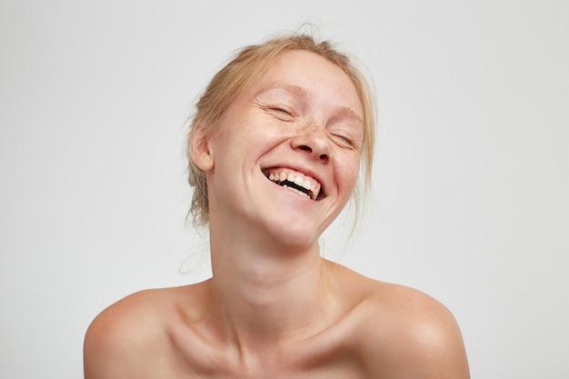 Knappe jonge mooie vrolijke roodharige dame met natuurlijke make-up die haar witte perfecte tanden laat zien terwijl ze breed lacht, poseren tegen een witte achtergrond