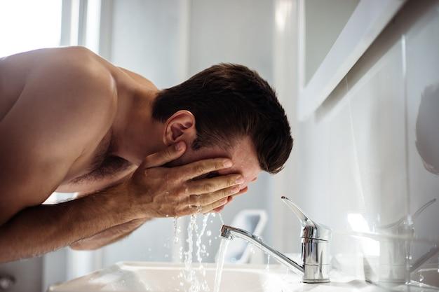 Knappe jonge naakte man wast zijn gezicht in de badkamer thuis.