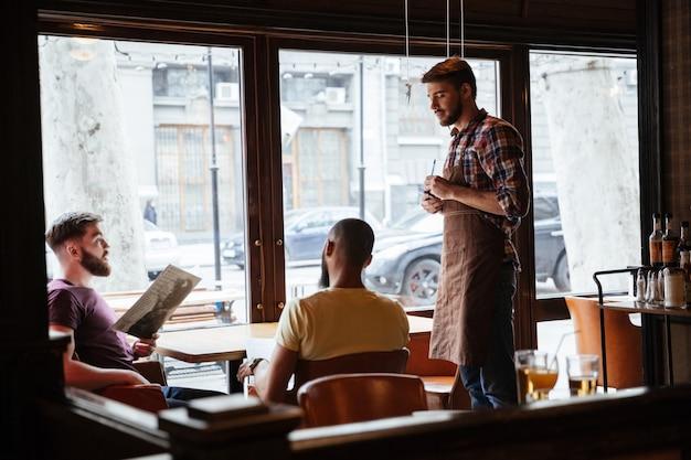 Knappe jonge ober die een bestelling opneemt van bezoekers in café