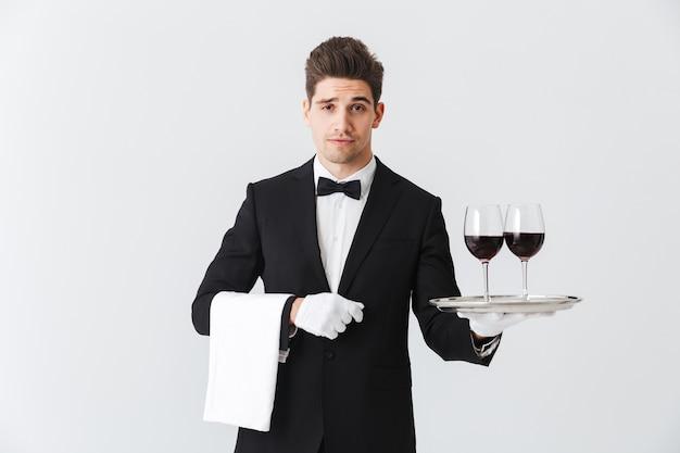 Knappe jonge ober die smoking draagt die een dienblad met twee glazen rode wijn voorstelt die over grijze muur wordt geïsoleerd