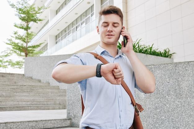 Knappe jonge ondernemer die in de straat loopt, aan de telefoon spreekt en de tijd controleert op zijn polshorloge