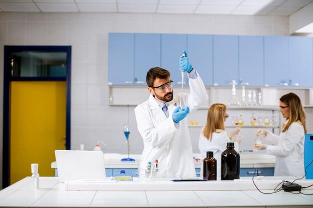 Knappe jonge onderzoeker in beschermende werkkleding in laboratorium analyseren kolf