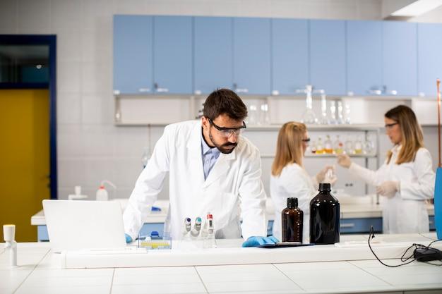 Knappe jonge onderzoeker in witte laboratoriumjas die met laptop in het laboratorium werkt