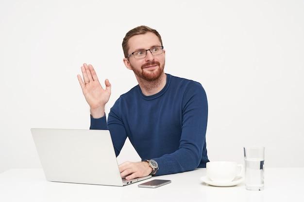 Knappe jonge ongeschoren blonde man gekleed in blauwe trui verhogen palm in hallo gebaar terwijl opzij kijken, werken met zijn laptop op witte achtergrond