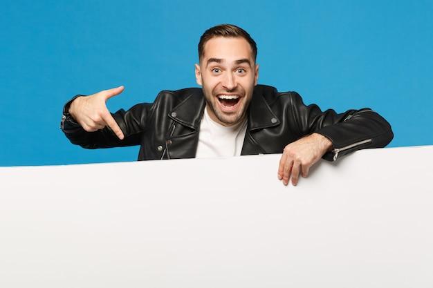 Knappe jonge ongeschoren man houdt grote witte lege lege billboard voor promotionele inhoud geïsoleerd op blauwe muur achtergrond studio portret. mensen oprechte emoties levensstijl concept. bespotten kopie ruimte