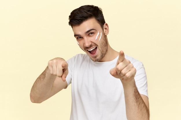 Knappe jonge ongeschoren man in wit t-shirt glimlachend en wijsvingers naar voren wijzend