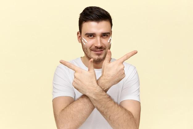 Knappe jonge ongeschoren man in wit t-shirt glimlachend en wijsvingers wijzend naar de zijkanten