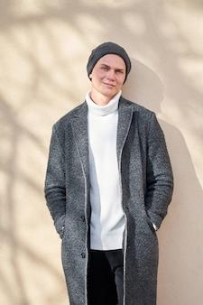 Knappe jonge positieve vrolijke hipster stijlvolle man met moderne grijze jas, witte trendy trui en zwarte spijkerbroek die zich in de buurt van beige muur bevindt