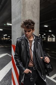 Knappe jonge professionele man in mode jeugdkleding in amerikaanse stijl met een lederen zwarte stijlvolle rugzak met een trendy kapsel dat op straat rust. aantrekkelijke stedelijke man poseren buitenshuis.