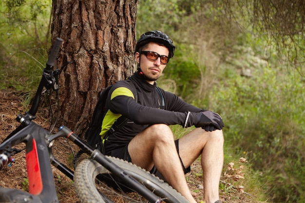 Knappe jonge professionele ruiter met bril en helm zittend onder boom, ontspannen en bewonderen prachtig uitzicht na ochtend fietsen training op motoraangedreven booster fiets in het weekend