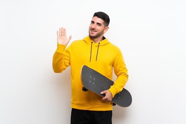 Knappe jonge schaatser man over geïsoleerde witte muur groeten met hand met gelukkige uitdrukking