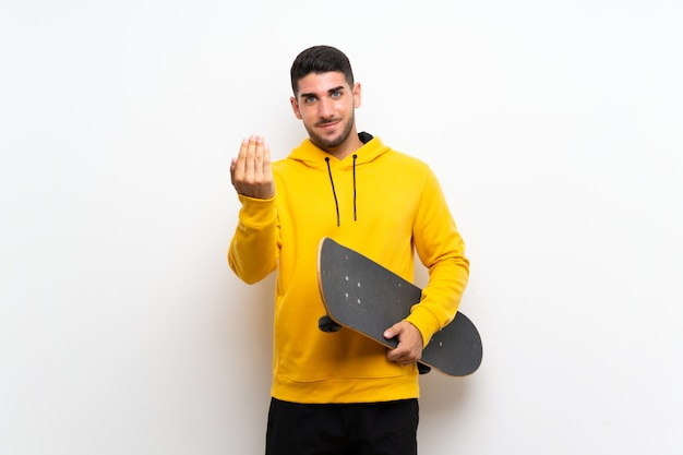 Knappe jonge schaatsermens op witte muur die met hand uitnodigt te komen