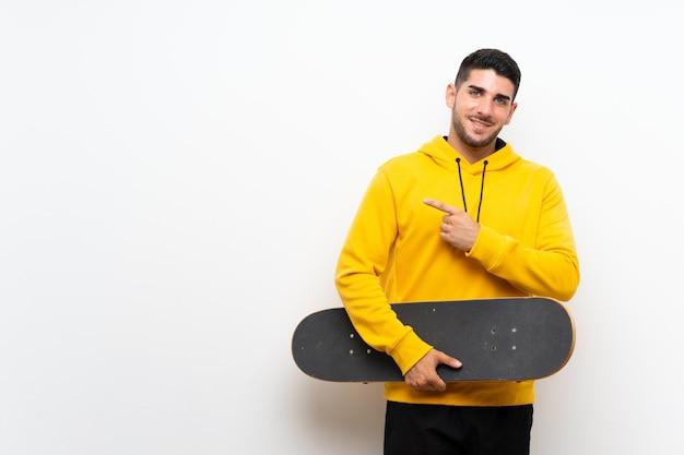 Knappe jonge schaatsermens over geïsoleerde witte muur die aan de kant richt om een product te presenteren