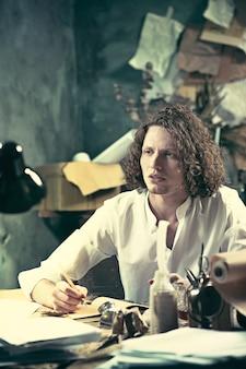 Knappe jonge schrijver die aan de tafel zit en thuis iets in zijn schetsblok schrijft