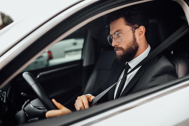 Knappe jonge serieuze bebaarde bestuurder in volledig pak met vastmakende veiligheidsgordel autorijden