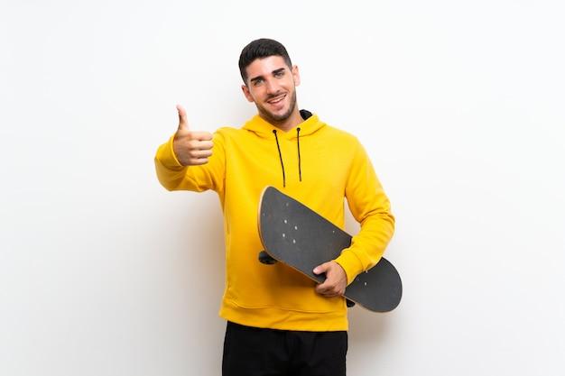 Knappe jonge skater man over witte muur met duimen omhoog omdat er iets goeds is gebeurd