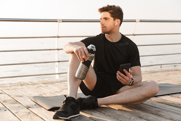Knappe jonge sportman buiten zitten luisteren muziek