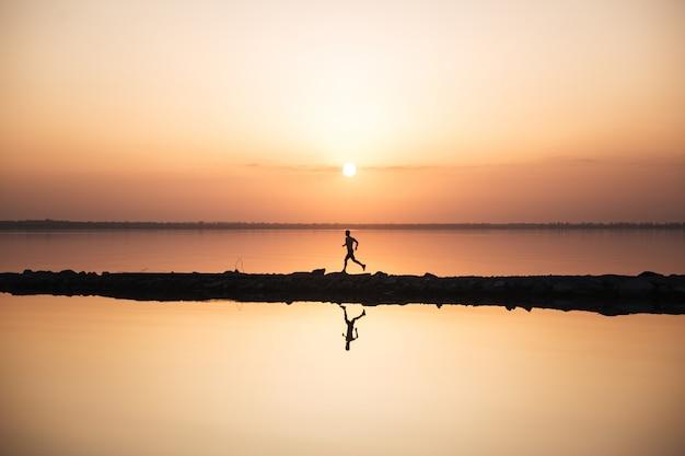 Knappe jonge sportman die bij het strand loopt