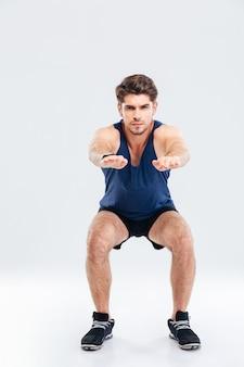 Knappe jonge sportman doet squats op witte achtergrond white
