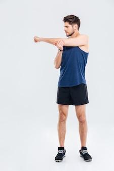 Knappe jonge sportman handen uitrekken tijdens training geïsoleerd op een grijze achtergrond
