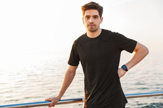 Knappe jonge sportman in zwart overhemd