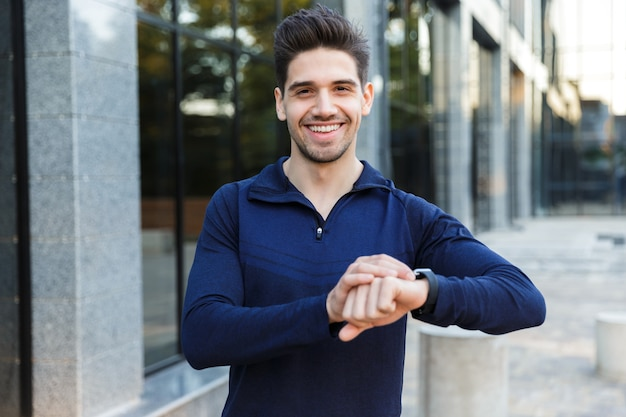 Knappe jonge sportman permanent buitenshuis, tijd controleren