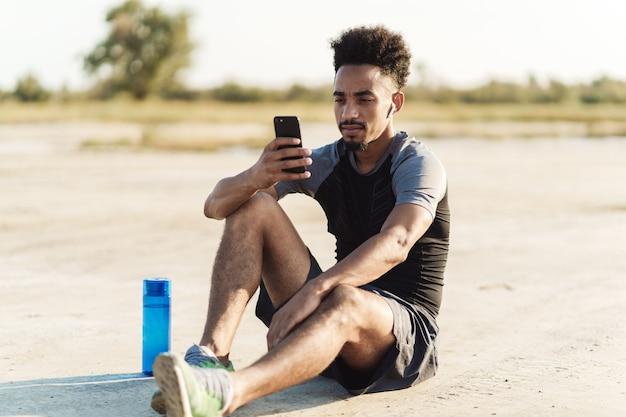 Knappe jonge sterke sportman luisteren muziek met koptelefoon buitenshuis met behulp van mobiele telefoon