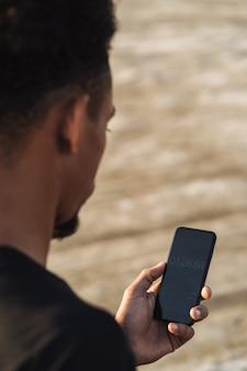 Knappe jonge sterke sportman met behulp van mobiele telefoon buitenshuis