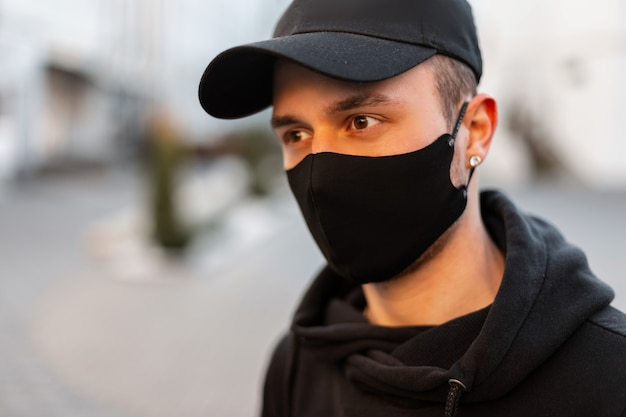 Knappe jonge stijlvolle man met een zwarte pet en een beschermend masker in een zwarte hoodie op straat