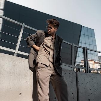 Knappe jonge stijlvolle man model met coole zonnebril in fashion grijs pak look met blazer en shirt in de stad bij zonlicht. mannelijke zakelijke stijl en schoonheid