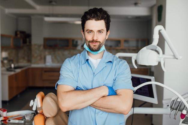 Knappe jonge tandarts in witte jas kijkt naar de camera en glimlacht terwijl hij met gekruiste armen in zijn kantoor staat.