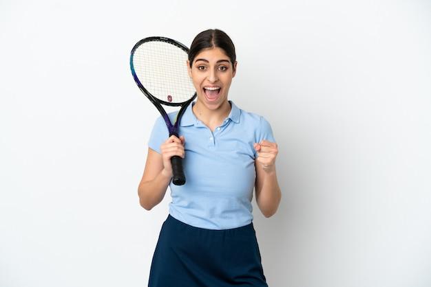 Knappe jonge tennisser blanke vrouw geïsoleerd op een witte achtergrond die een overwinning viert in winnaarspositie
