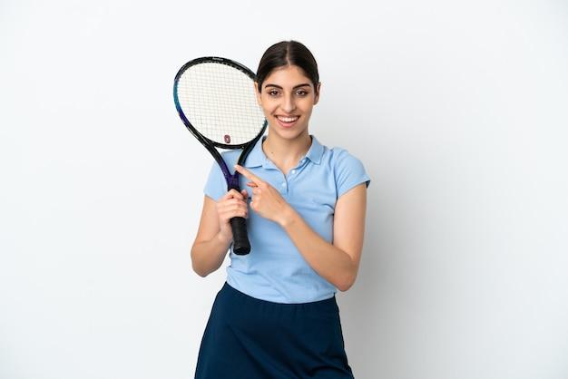 Knappe jonge tennisser blanke vrouw geïsoleerd op een witte achtergrond wijzend naar de zijkant om een product te presenteren