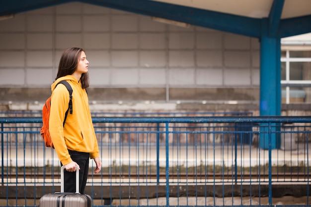 Knappe jonge toerist die op de trein wacht