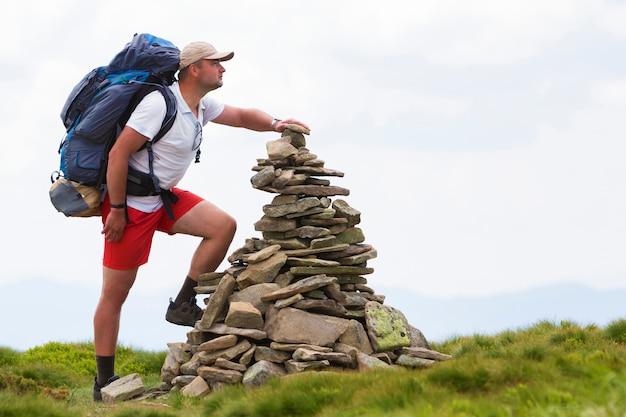 Knappe jonge toeristenmens die met rugzak piramidestapel van stenen maken aangestoken door het heldere groene gras van de de zomerzon. toerisme, reizen en landmark concept.