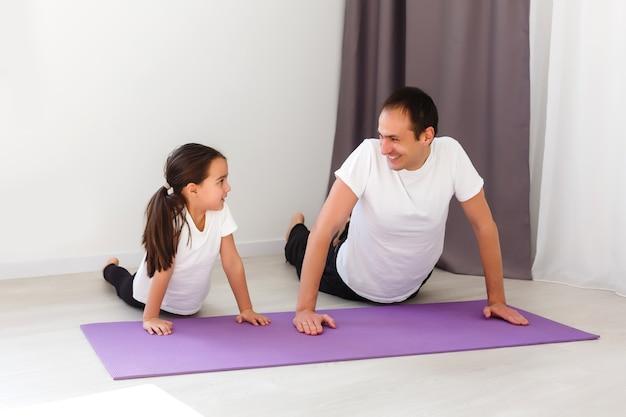 Knappe jonge vader en zijn schattige dochtertje doen reverce plank met beenverhoging op de vloer thuis. gezinsfitnesstraining.