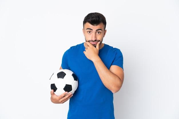 Knappe jonge voetballer man over geïsoleerde muur denken