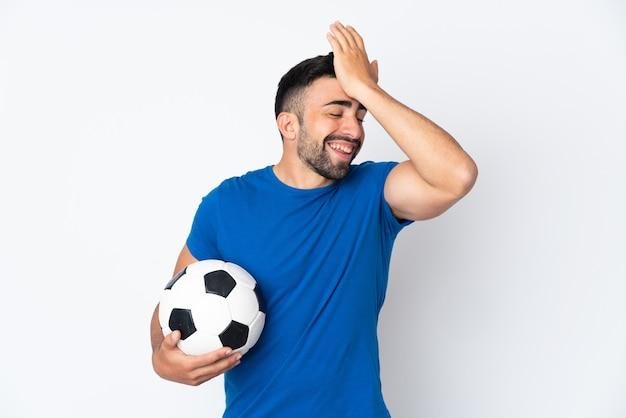 Knappe jonge voetballer man over geïsoleerde muur heeft iets gerealiseerd en de oplossing voor ogen