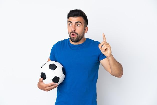 Knappe jonge voetballermens over geïsoleerde muur die de oplossing wil realiseren terwijl hij een vinger opheft