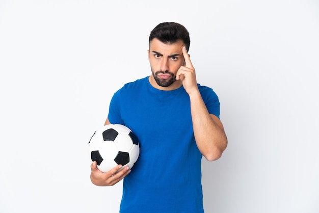 Knappe jonge voetballermens over geïsoleerde muur die een idee denken